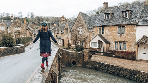 Woman balancing on bridge Castle Combe Wiltshire England 560x315
