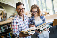Two_happy_students_with_books_in_the_library_